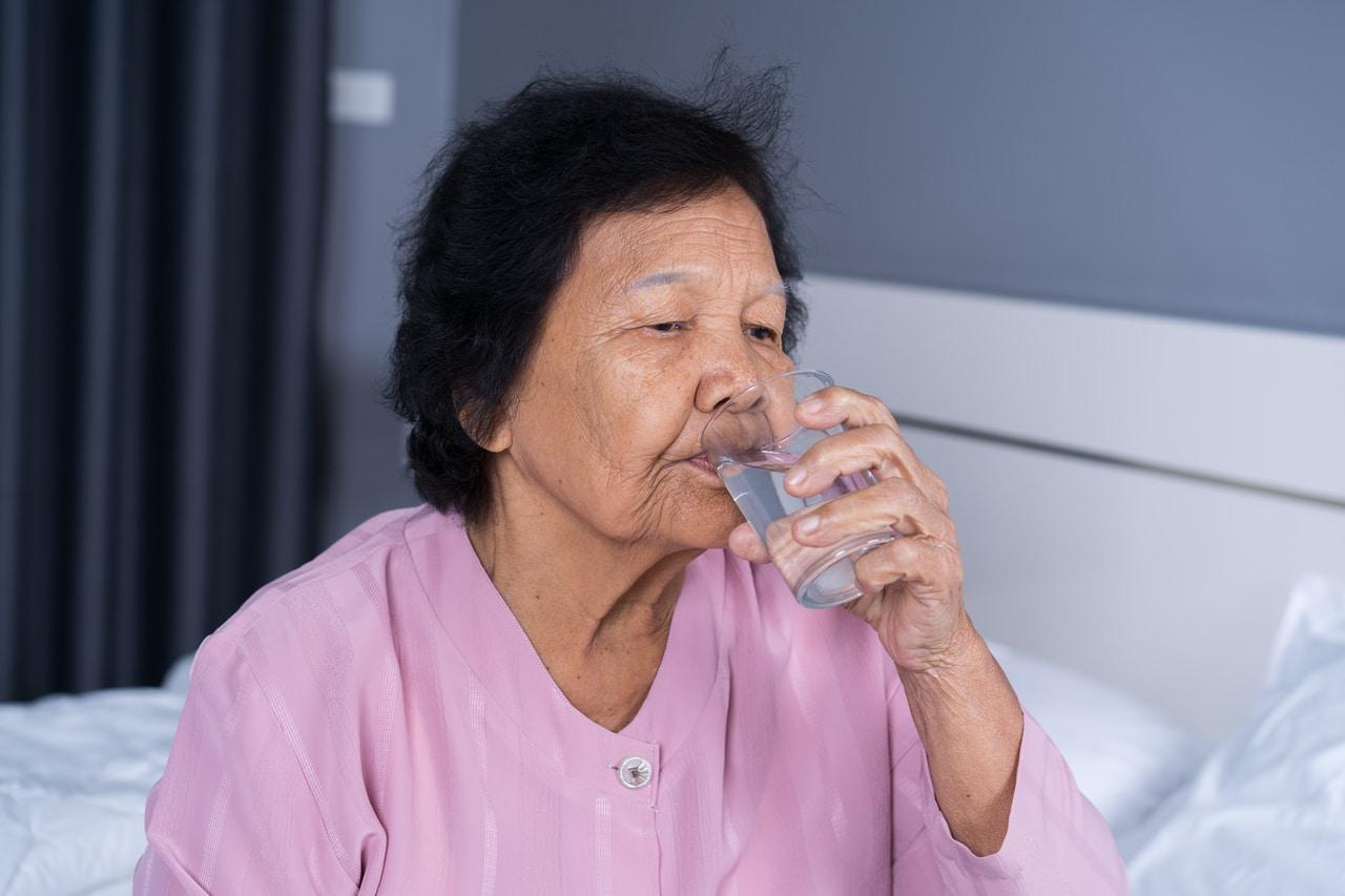 A senior woman taking her prescribed medicine